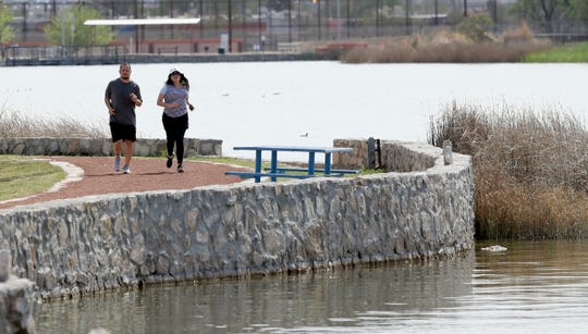 A couple takes a run around Ascarate Lake on Tuesday afternoon, just a day before the city closed parks and golf courses to curb the spread of the coronavirus.