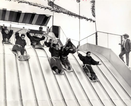 A group of singing seminarians from St. Anthony's Seminary in El Paso enjoy a bit of relaxation at the Bassett Center Super Slide. They are shown singing at the Center in the Mall in this Aug. 27, 1968, photo.