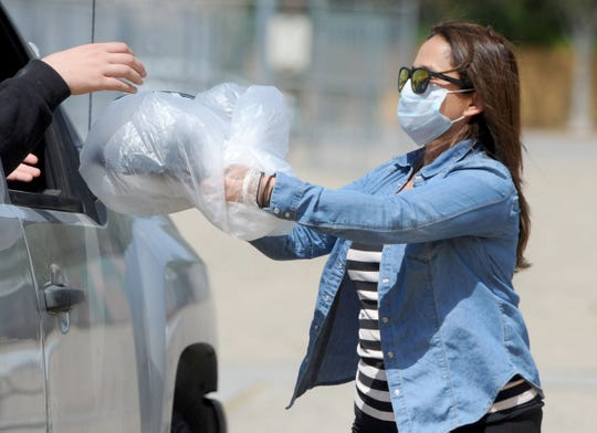 Ivonee Carrion, with the Simi Valley Unified School District, passes out laptops in plastic bags to students inside their cars Thursday, April 2, 2020.