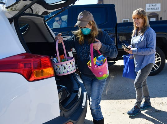 Lori Staas, owner of Jersey Girl Farm Market on Mays Landing Road in Vineland, delivers pre-ordered Easter baskets to a customer on Thursday, April 2, 2020.