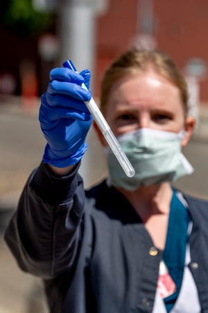 Kaweah Delta nurse Jennifer Harper is among nurses collecting nasal swab samples for COVID-19 testing on Thursday, April 2, 2020 at outdoor drive-up collection stations on Floral Street in Visalia, Calif. Appointments are required.