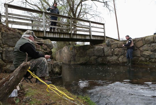 Pat Dodds of Bear (left) and his son, Chris Dodds of Pike Creek fish on opposite banks of Wilson Run at Brandywine Creek State Park on the first day of trout season Tuesday. Dropping a line in from the bridge is Trampas Henderson of Stanton.
