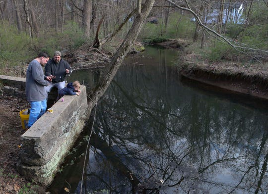 Zachary Colatriano (left), his father, Larry, and son, Anthony, 2, try their luck on Wilson Run at Brandywine Creek State Park on the second day of trout season Wednesday. The traditional opening day of the season was moved up to Tuesday of this week from the first Saturday in April.