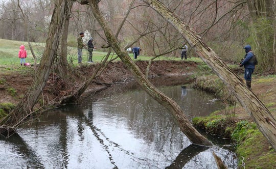 People fish in Brandywine Creek State Park on the first day of trout season Tuesday. The opening day was moved up from its traditional first Saturday in April.