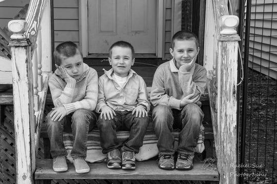 The Arendt brothers, Landon, 9, right, Evan, 7, left, and Ian, 6, middle, pose for a photo on their porch.