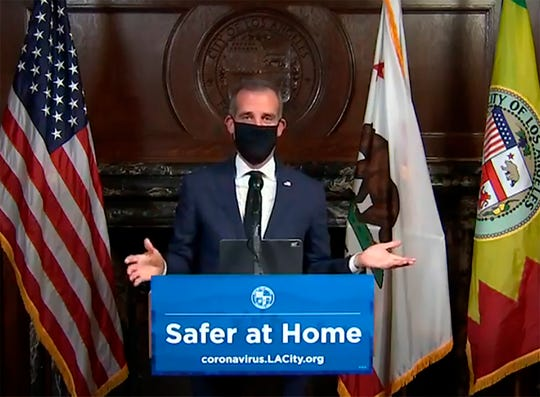 Los Angeles Mayor Eric Garcetti wears a face mask during his Wednesday news conference while recommending that the city's 4 million people do the same when going outside amid the spreading coronavirus.