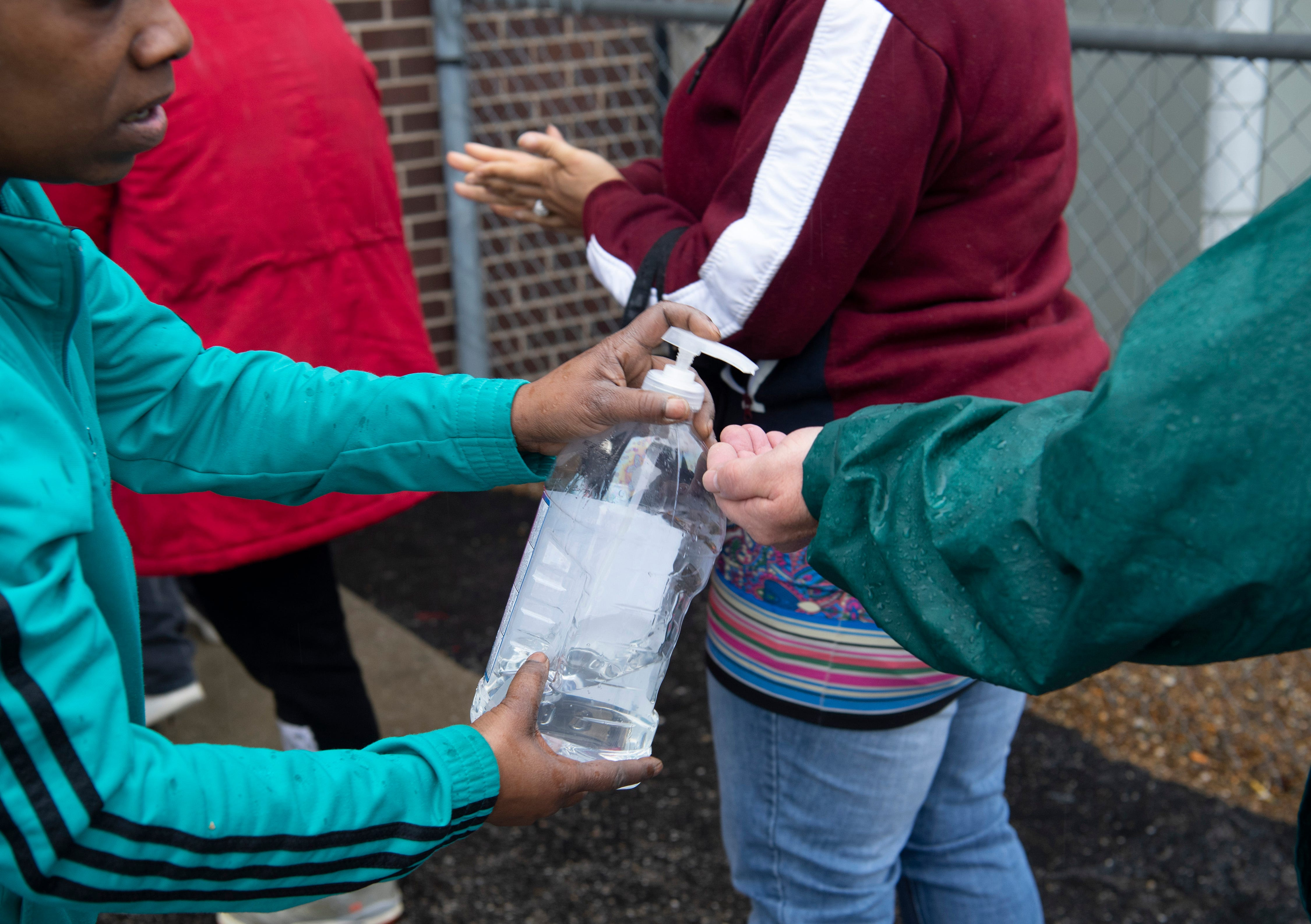 Even as the coronavirus pandemic brought out some of Americans' deepest fears, it also summoned their better angels. In Evansville, Ind., Lashawn Miles offers squirts of hand sanitizer to people who gathered for Salvation Army lunch program March 18.