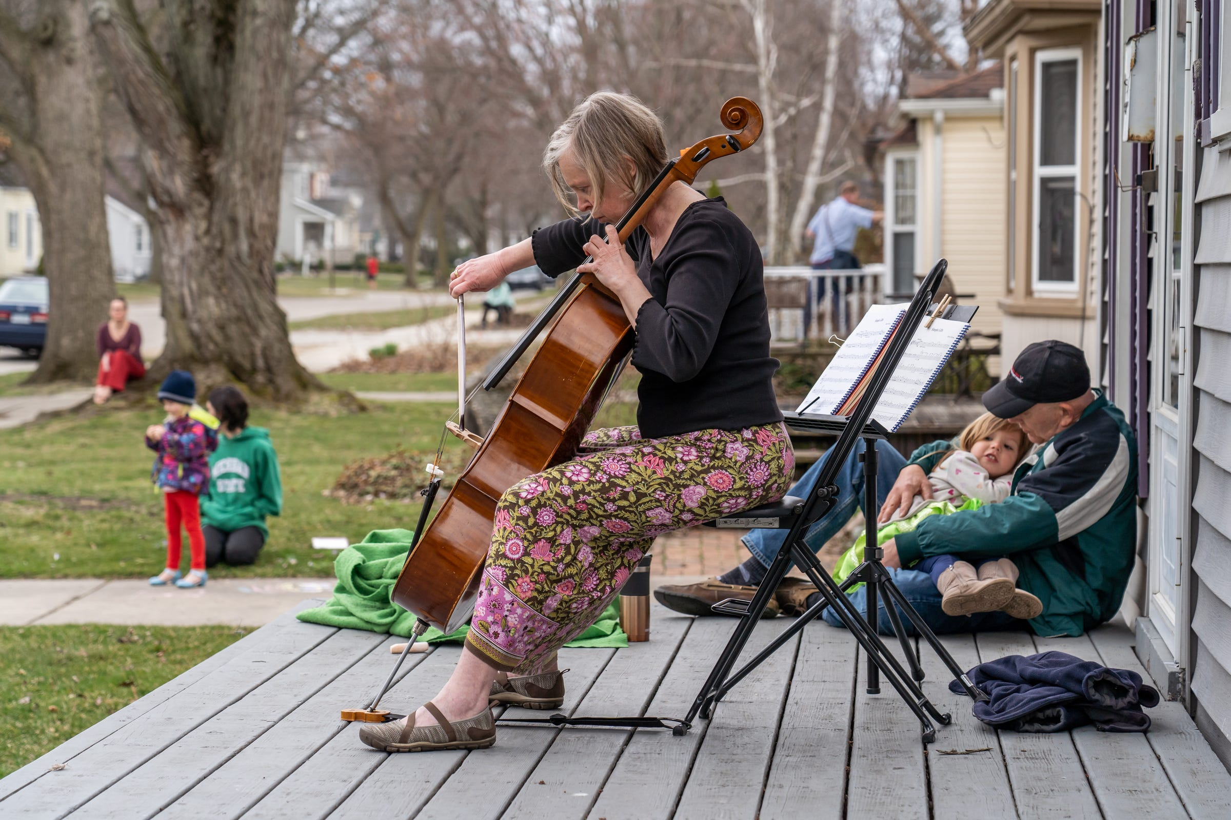 Irina Tikhonova plays the cello on her front porch in Royal Oak, Mich. for neighbors and people passing by as he husband Fred Trimble holds their 4-year-old granddaughter Mia on March 26, 2020. Before the coronavirus pandemic prompted concert cancellations, Tikhonova, who has been playing the cello for more than four decades, played the with local symphony orchestras. Now, she is giving 30-minute porch performances in her Royal Oak neighborhood weather permitting.