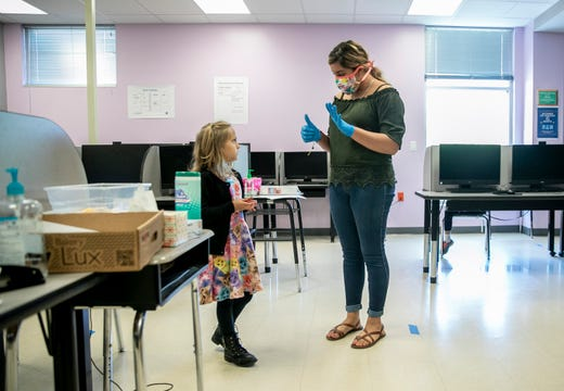 Lorena Dominguez, a campus operations specialist at the IDEA Rundberg charter school in Austin, Texas, teaches math to kindergartener Reighan Holzkamp, 6, on Wednesday April 1, 2020.  Ten children of first responders and essential workers are being taught at the school amid the coronavirus pandemic.