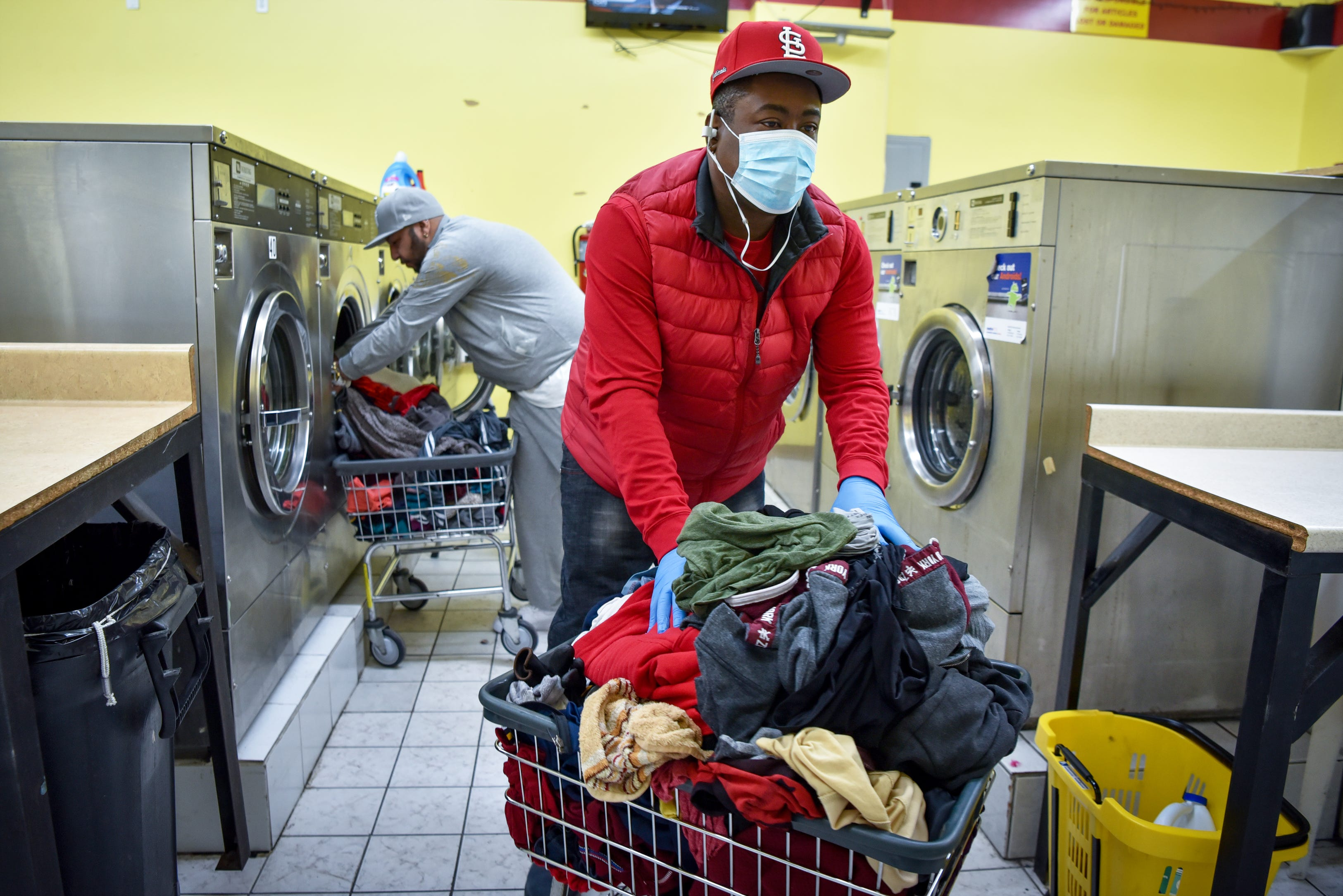 Daily routines must continue, Sammy Irizarry of Passaic, wears a mask and gloves as a precaution against COVID-19 while washing his clothes at Tri-City Laundromat in Passaic, N.J. on March 22, 2020. Irizarry has preexisting health conditions, including diabetes and high blood pressure and is still working.
