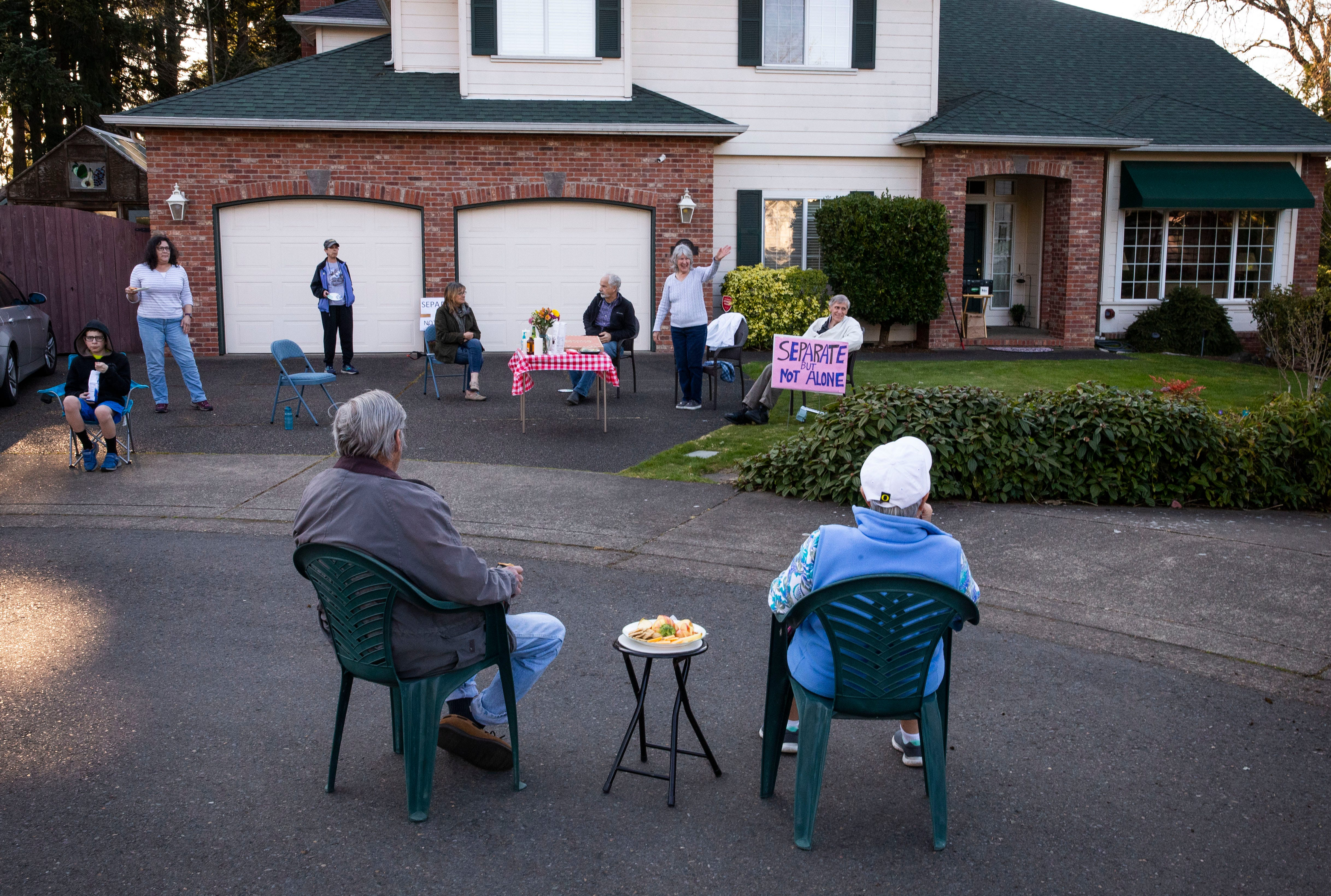 Communities made the best of lockdowns as Americans pulled together to fight the spread of the virus. In Eugene, Ore., Mary Lou Vignola, center, waves to her neighbors during a socially distant block party she and her husband, Frank, helped organize March 21.