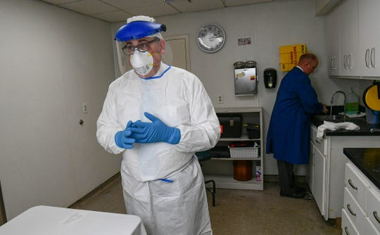 """Kristopher Smith, left, and Andrew Weatherford, right, funeral directors and embalmers at McDougald Funeral Home, puts on a set of gear and wash hands regularly for """"adequate protection for universal precaution,"""" before embalming at the home in Anderson Friday."""