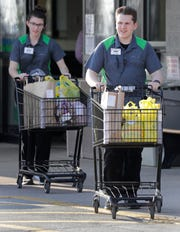 Festival Foods employees Kayla Murray, left, and Teddy Rusch bring out carts full of customers groceries to the dedicated ClickNGo parking spot Thursday in Appleton.