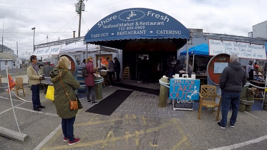 People wait to be helped during the outdoor market at Shore Fresh Seafood Market in Point Pleasant Beach Friday, April 3, 2020.