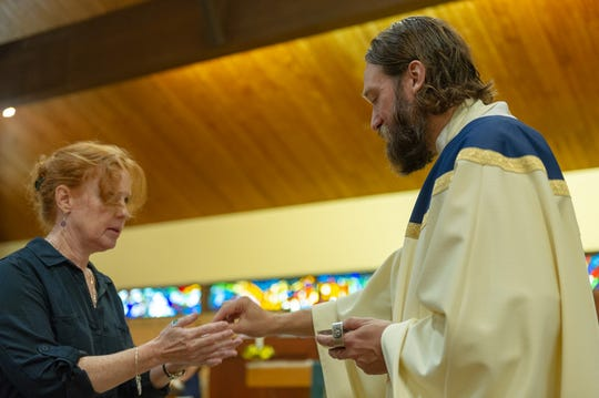 Father Dave Swantek distributes Communion at St. Martha Church in Point Pleasant in 2018.