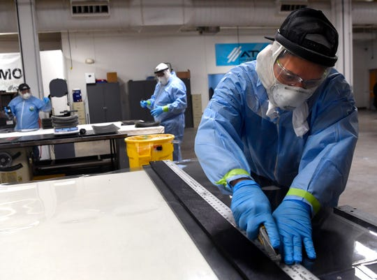Scott Lowery cuts lengths of sheet plastic Friday at Tigé Boats. The company has retooled to make personal protective equipment in the form of face shields and cloth masks during the pandemic.