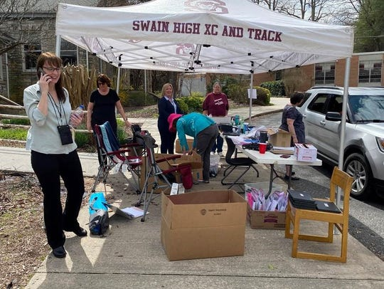 Swain Middle School staff distributing Chromebooks and phsycial work packets to families driving by.