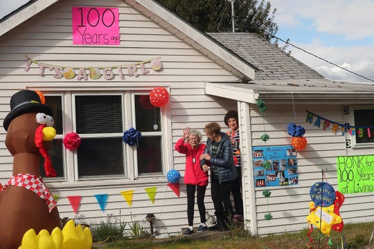 "Doris Nielsen, 100, gives a wave to those gathered in front of her Port Orchard home as she exits the front door with neighbor Lynn Olson and caretaker Dora Cantu on Thursday. Neighbors, family and friends decorated Nielsen's home, waved signs and serenaded her with ""Happy Birthday"" from the street and sidewalk."