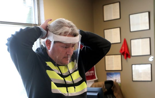 Rick Wood puts on a face shield that his company Tarp Innovators in Poulsbo is working on for local first responders.