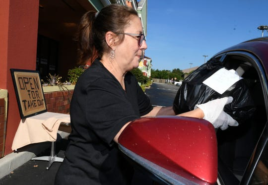 Gina Pierce of Tuscany Grill takes a to go order to a customer at the restaurant in SuntreeMandatory Credit: Craig Bailey/FLORIDA TODAY via USA TODAY NETWORK