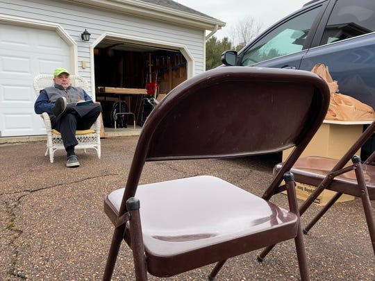 Kurt Simmers of Williston waits for family to arrive with chairs set, more than the required six feet of distance apart from him. He is one of the homeowners participating in the teddy bear scavenger hunt, with two bears in his home's windows. Photo April 3, 2020.