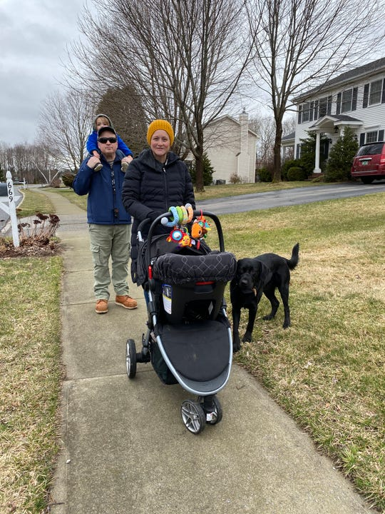 Babette and Ryan Howe, with kids Marty and Jack and Bear the dog, stroll through the neighborhood where many houses have displayed teddy bears in the windows for a community-wide scavenger hunt. The effort is designed to create connection in a time of distancing due to the pandemic. Photo April 3, 2020.