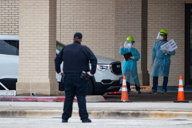 Heath care workers conduct COVID-19 testing at the Corpus Christi's drive-thru testing center at the old Christus Spohn Memorial Hospital parking lot on Friday, April 3, 2020.
