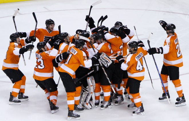 Philadelphia Flyers players celebrate after winning a shootout against the New York Rangers, Sunday, April 11, 2010.