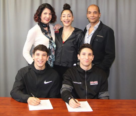 Delsea seniors and twins Marco, sitting left, and Nico Morales, sitting right, sign their national letters of intent to pole vault at Rutgers. Standing (from left): Christian Morales (mother), Mercedes Morales (sister) and Angel Morales (father).