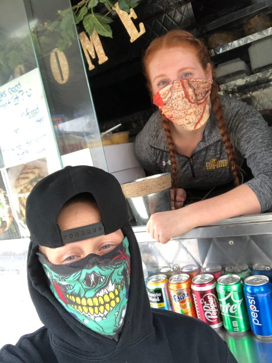 Food truck owner Megan Hilbert inside her Red's Rolling Restaurant and food trucker Sabrina Brill of Not My Mama's Tacos wear colorful protective masks as they await their health care customers outside Cooper University  Hospital in Camden during the ongoing coronavirus pandemic.