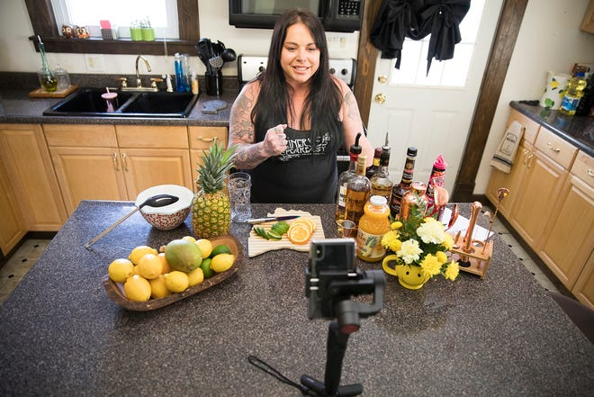 Steiner's Speakeasy owner Tara Gillum shows her Facebook audience of over 1000 how to make a version of a Zombie cocktail drink to her viewers.