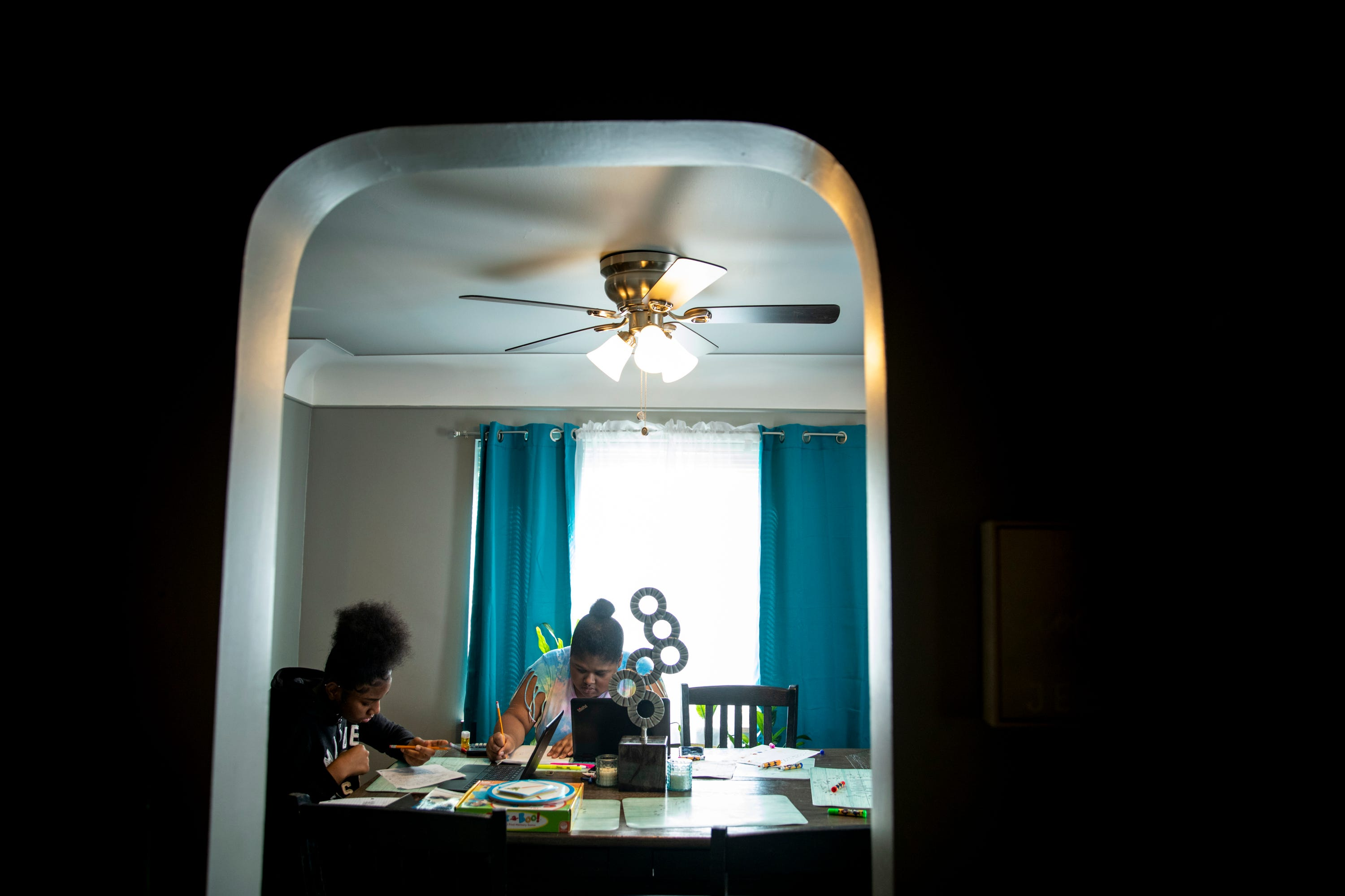 Sisters Destiny Taylor, 12, and Curiah Simpson, 18, work on their school work at the dining room table in their home in North College Hill on Thursday, April 2, 2020. Destiny is in the seventh grade at Mt. Healthy Jr. High School. Simpson is a senior at Diamond Oaks.