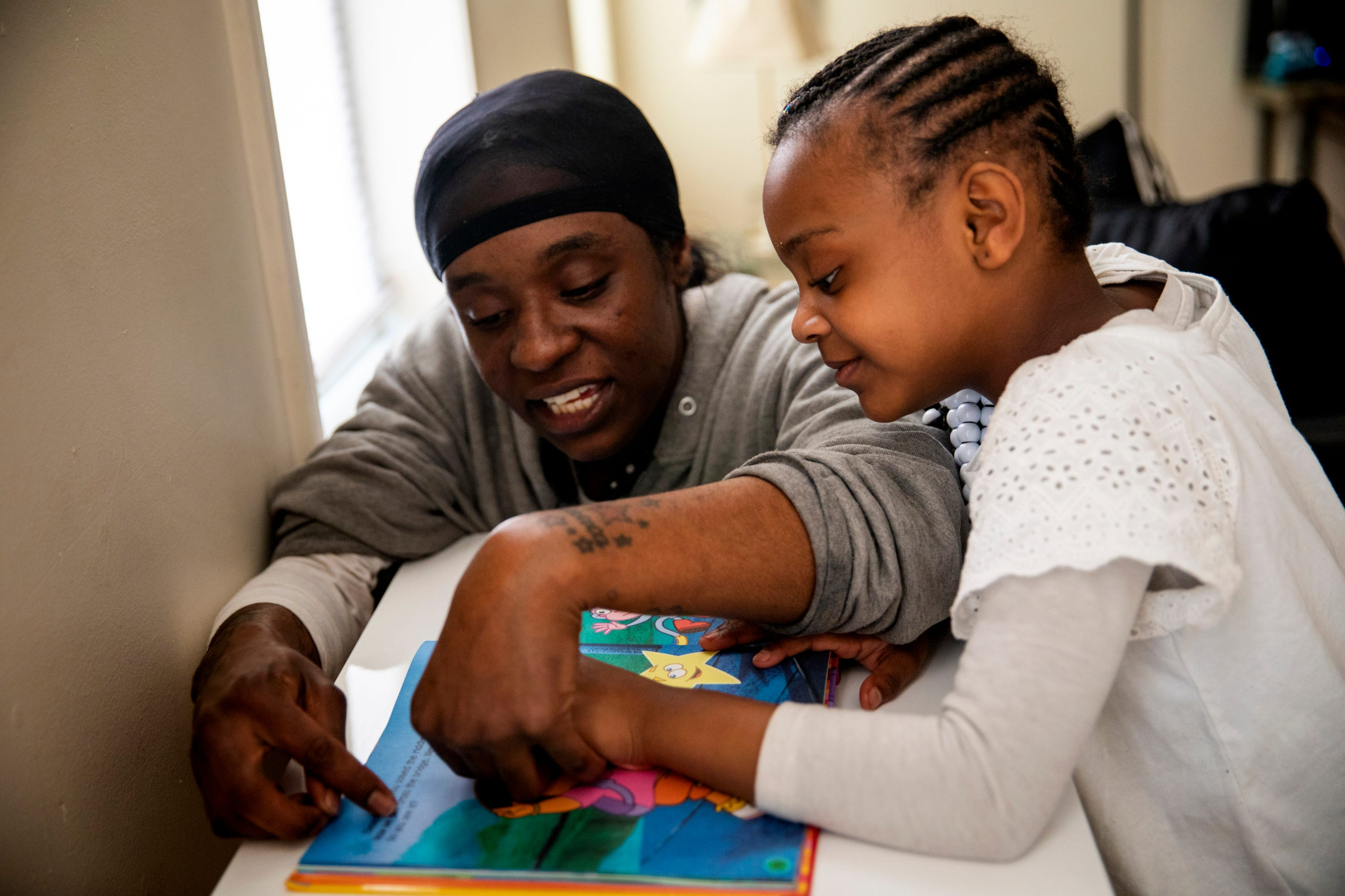 Renee Oliver reads with her daughter Keylah Wagoner, 5, in their apartment in Lower Price Hill on Thursday, April 2, 2020.