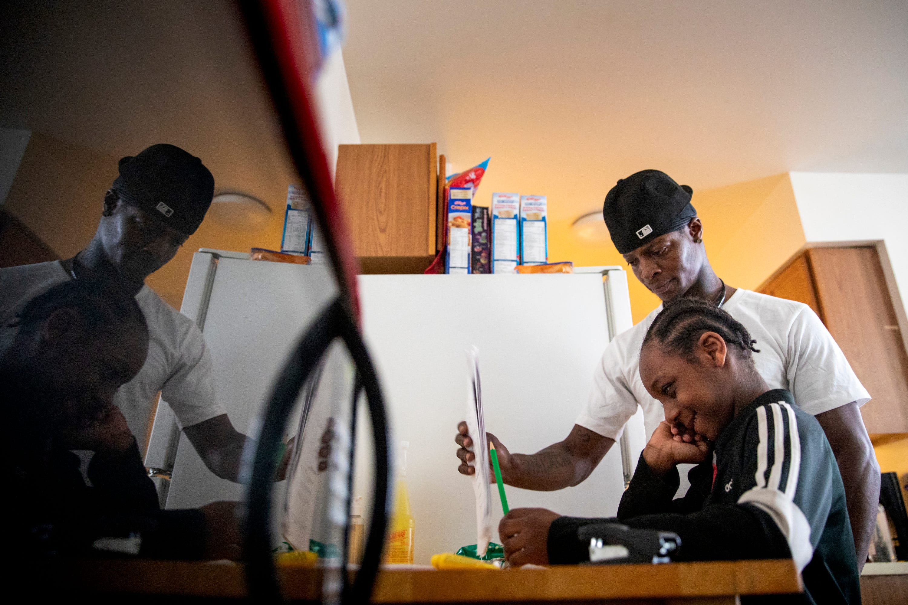 Sinaca Wagoner, Sr., helps his son Sinaca Wagoner, Jr., 7, with his school work in their apartment in Lower Price Hill on Thursday, April 2, 2020. Sinaca Jr. is in the second grade at Cincinnati College Preparatory Academy.