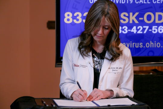 Ohio Department of Health Director Dr. Amy Acton signs an extension of the state's stay-at-home order on April 2, 2020.