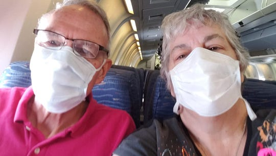 Rob and Andrea Anderson take a selfie on an airplane on Friday, April 3. They are finally headed home after being quarantined in their room on a cruise ship for more than a week.