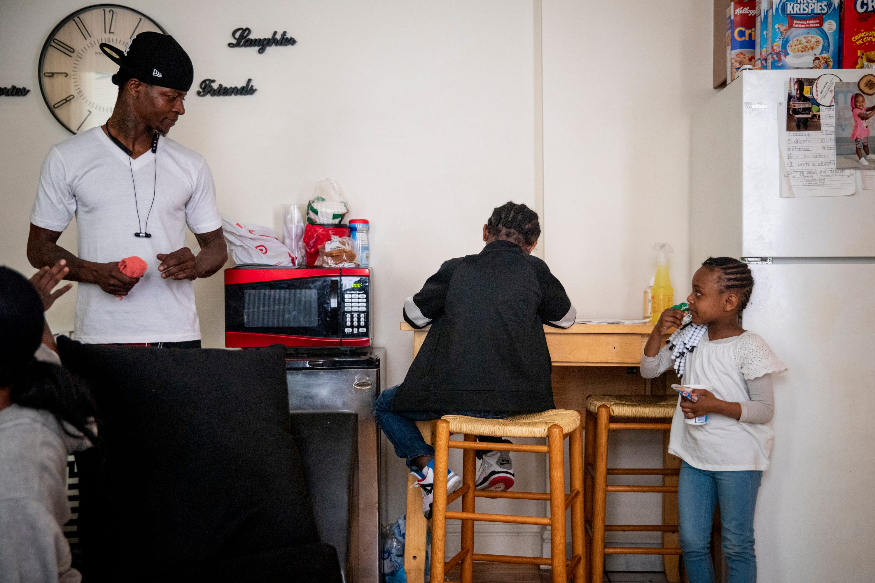 Sinaca Wagoner, Jr. 7, works on his school work while his dad and sister watch in their apartment in Lower Price Hill on Thursday, April 2, 2020. Sinaca Jr. is in the second grade at Cincinnati College Preparatory Academy.