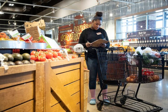 Online shopper Mariah Harris picks up items in the fresh produce section for an order at Busch's Fresh Food Market in Canton on Friday, April 3.