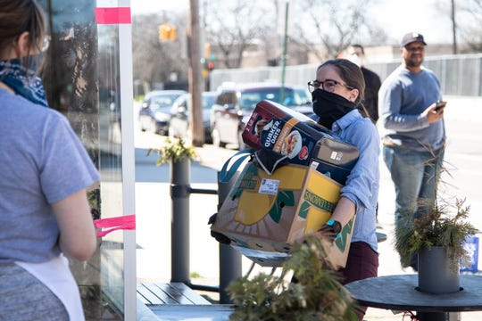 Julie Burtch of Detroit picks up her groceries outside of Sister Pie in Detroit, Friday, April 3, 2020.