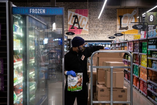 Grocery stores like Kroger and Busch's are trying to convince shoppers to keep their distance to keep everyone safe. Johnny Ali, restaurant supervisor at Busch's Fresh Food Market in Canton stocks the frozen goods section, Friday, April 3, 2020.