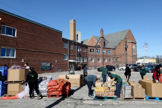 Members of Gleaners Community Food Bank along with Matrix Human Services prepare to get food ready for cars showing up at the Matrix facility in Detroit on Friday, April 3, 2020., for their bi-weekly food distribution to families in need.