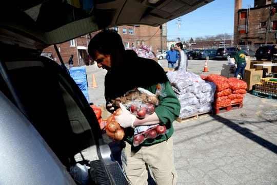 Jake Williams, the program manager for Gleaners Community Food Bank, adds a variety of food into the back of a minivan during the food drive they did with Matrix Human Services at Matrix's facility in Detroit on Friday, April 3, 2020, during their bi-weekly food distribution to families in need.