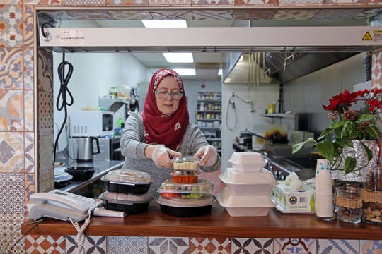 Chef Nahed Lotf boxes a to-go order at her Syrian restaurant Pattternz in Sterling Heights on Sunday, March 29, 2020.