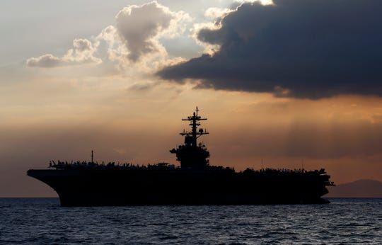 FILE - In this April 13, 2018, file photo the USS Theodore Roosevelt aircraft carrier is anchored off Manila Bay west of Manila, Philippines.