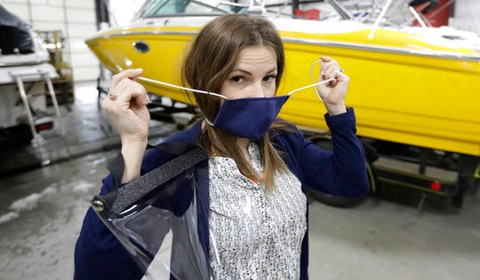 Romy Humphries holds a face mask at SugarHouse Industries in this March 26, 2020, file photo, in Midvale, Utah. SugarHouse Industries, a Utah company that usually manufactures boat tops and covers, has reconfigured its operation amid the spread of the coronavirus to produce face shields and masks.