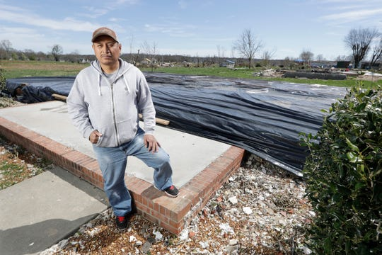 In this March 26, 2020, photo, Jose Cojom stands on the front step of what remains of his home after it was destroyed by a tornado in Cookeville, Tenn.