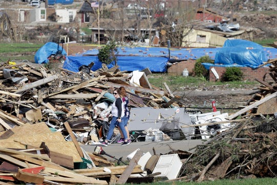 In this March 26, 2020, photo, people walk down a street lined with tornado debris in Gallatin, Tenn. Thousands of people in Middle Tennessee affected by the deadly twisters of March 3 now also have to confront life in the age of coronavirus.