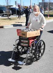 Danielle Sirekis,  patient representative,  Beaumont Hospital, Royal Oak, uses a wheelchair to deliver meals delivered by members of Front Line Appreciation Group, Friday, April 3, 2020.