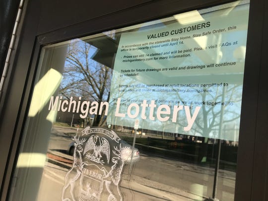 "The front door of Michigan Lottery office in downtown Lansing is shown on Friday, April 3, 2020. A notice on the door says, ""Tickets may still be purchased at retail locations permitted to remain open."""