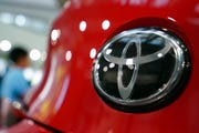 In this Aug. 2, 2019, file, photo, people walk by the logo of Toyota at a show room in Tokyo.
